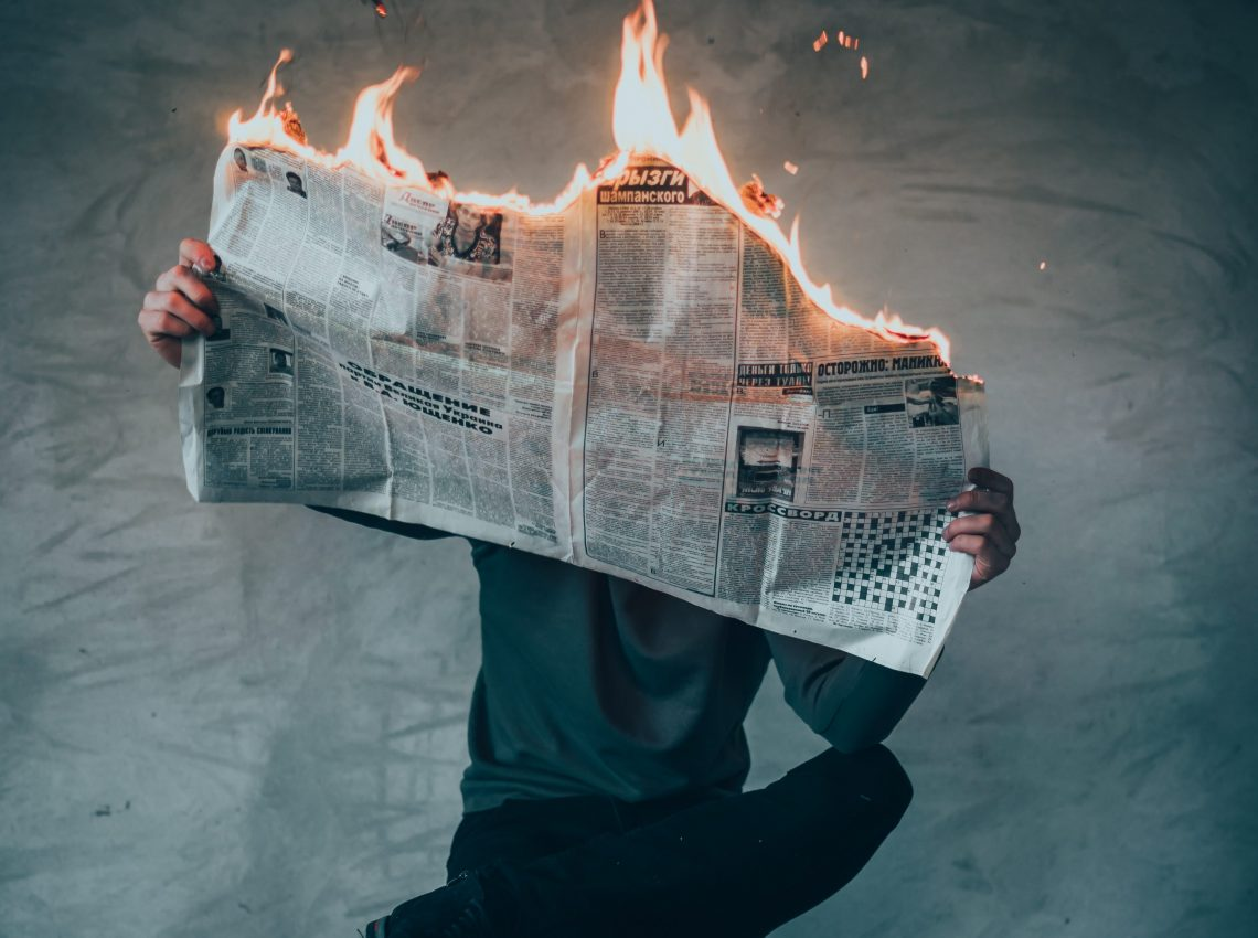 Person Holding Burning Newspaper